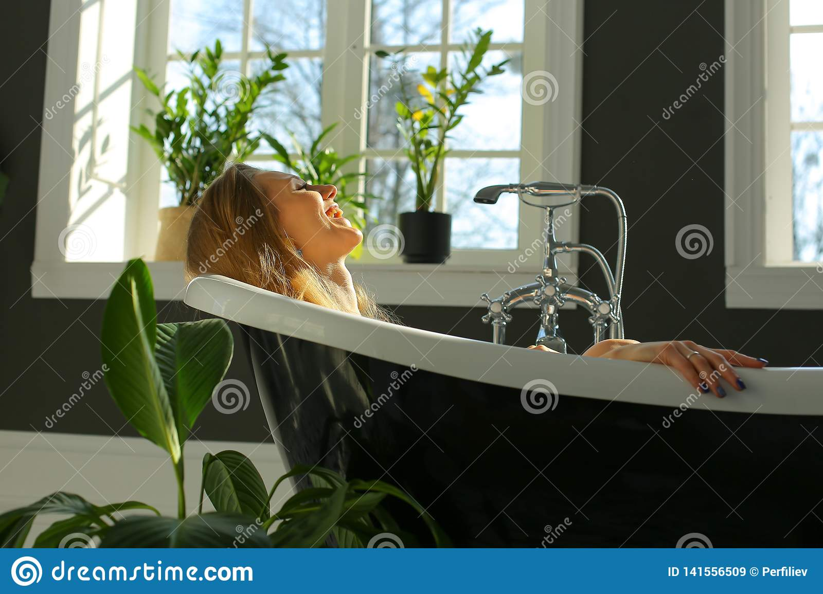 Smiling woman is relaxing in bath