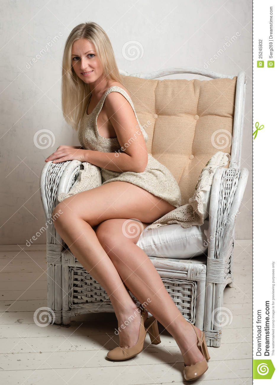 Smiling Woman In Short Dress Is Posing On A Chair Stock