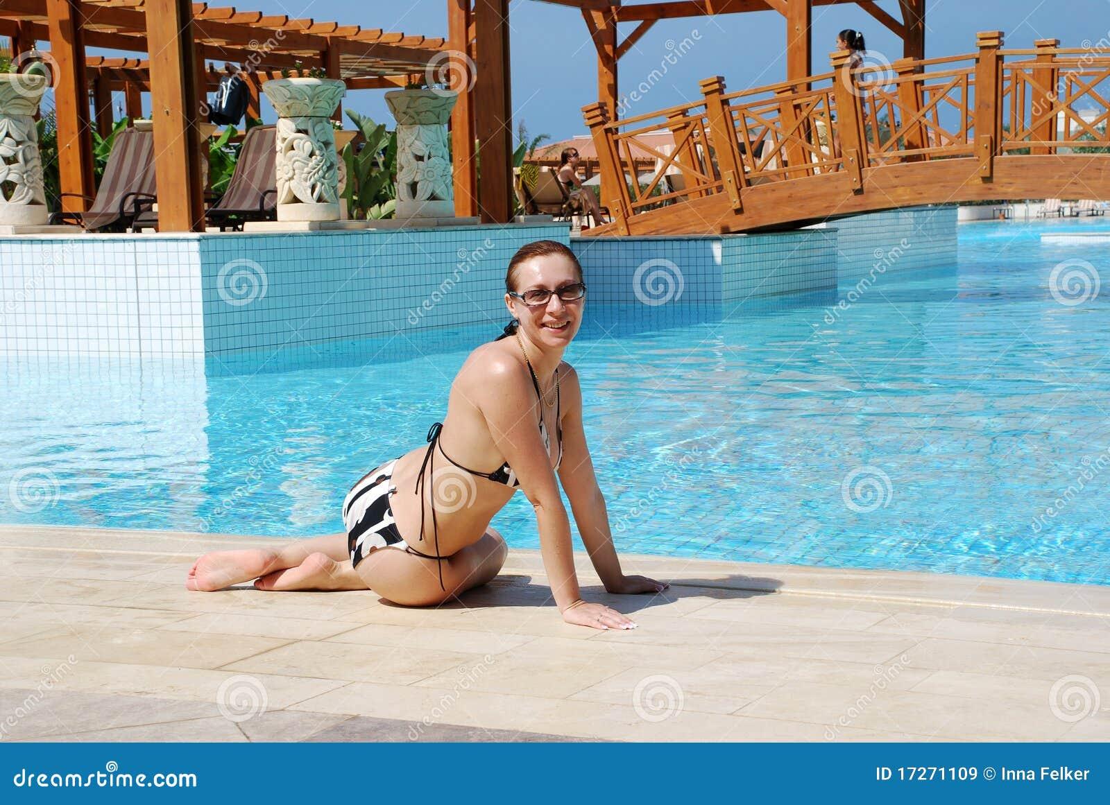 Smiling woman sitting near swimming pool