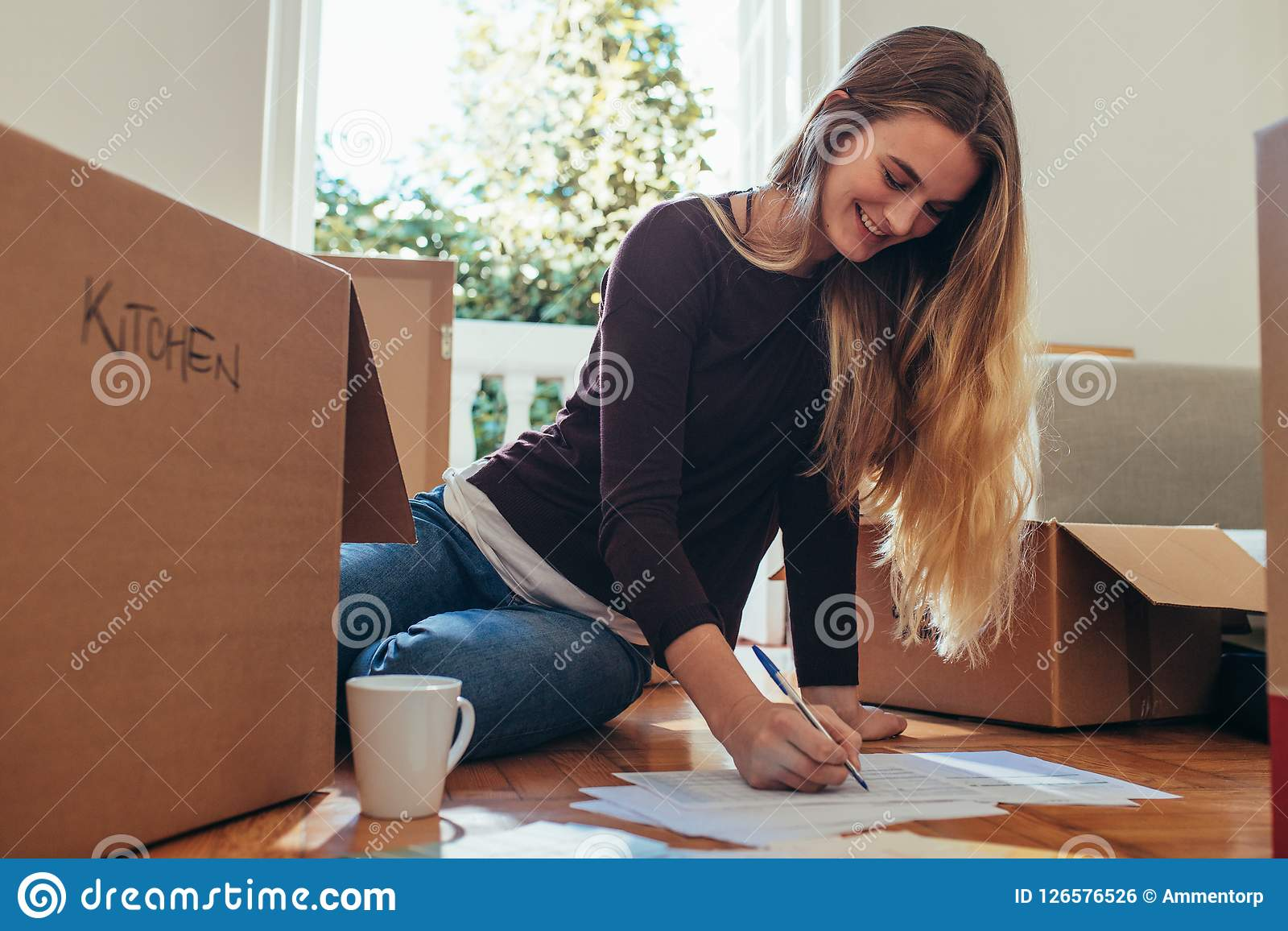 Smiling Woman Sitting With Packing Boxes On Floor Making A List