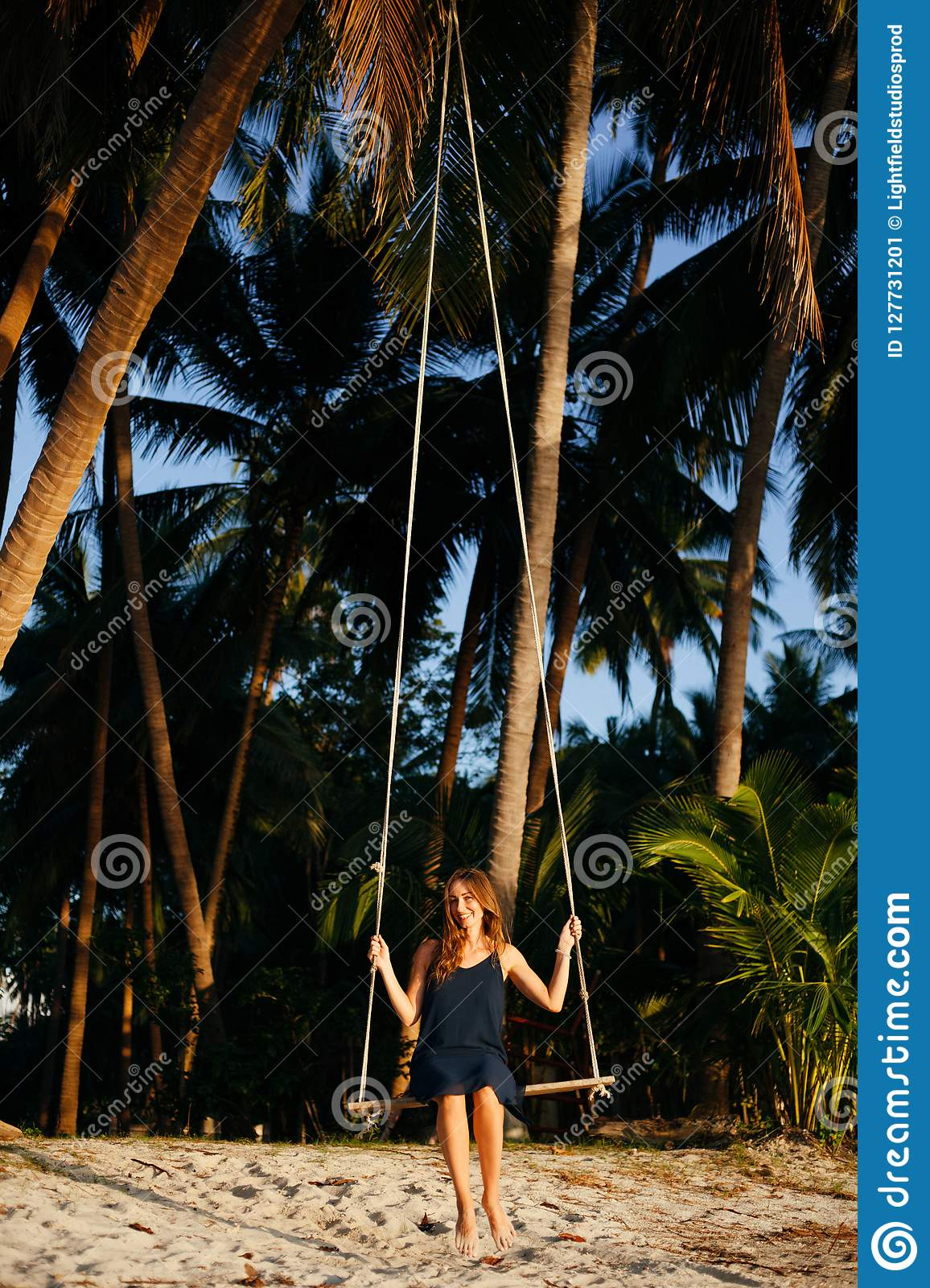 Smiling Woman Sitting On Swing Between Palm Trees At Beach ...
