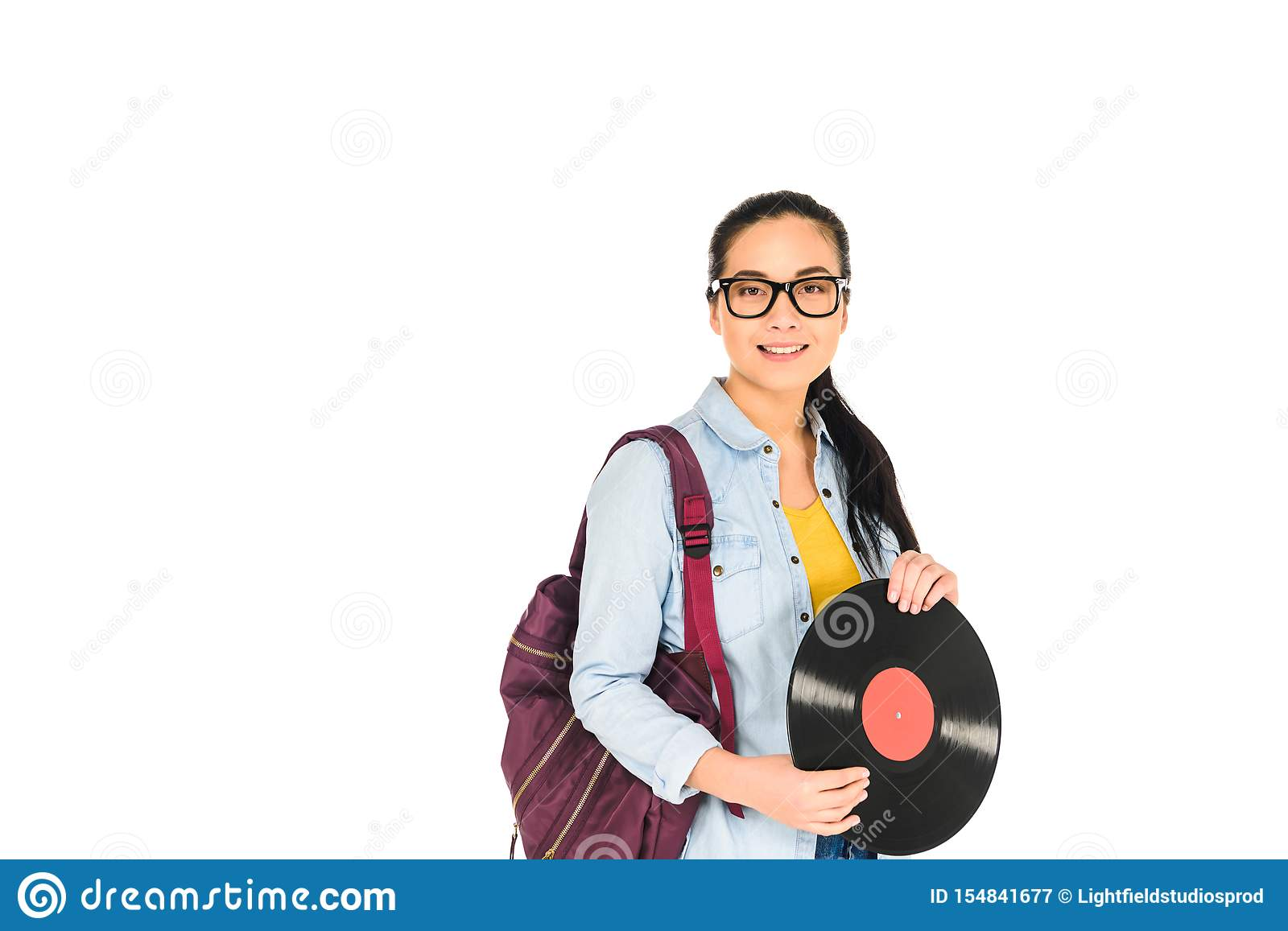 smiling woman standing with backpack and holding vinyl record in hands isolated