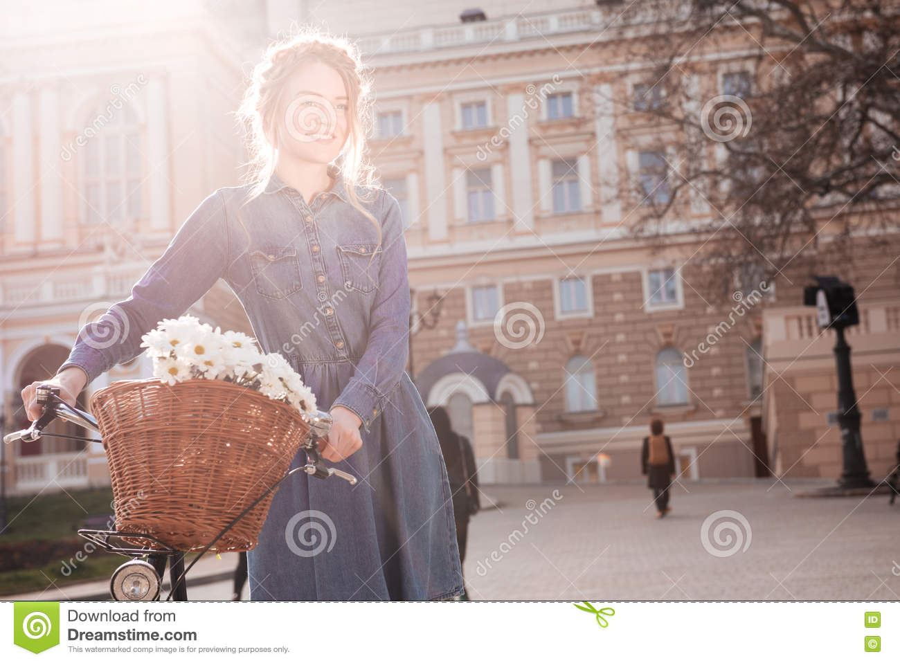 Smiling woman standing with bike in the city
