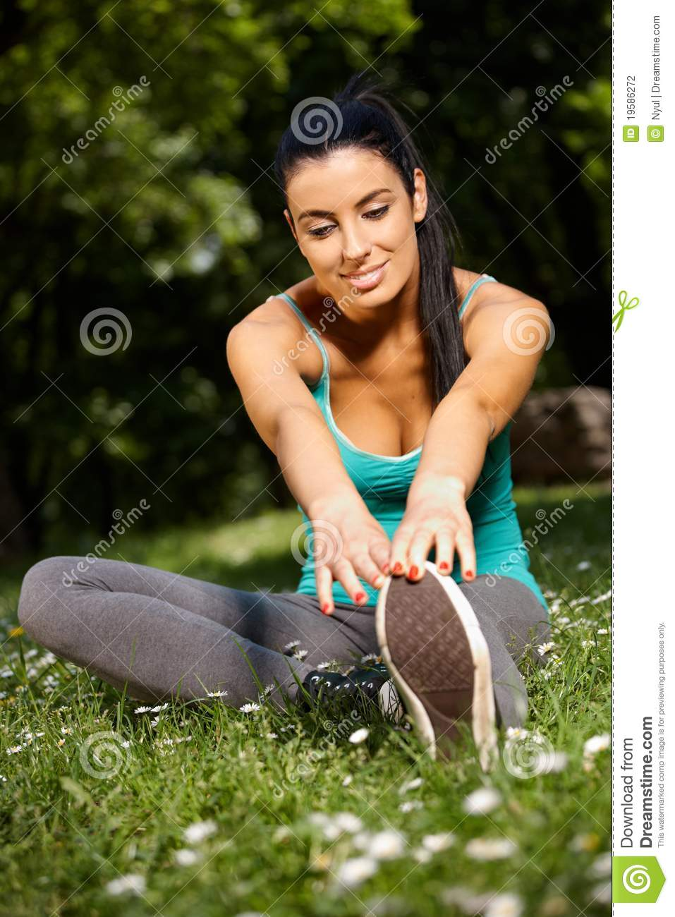 Smiling woman stretching in park