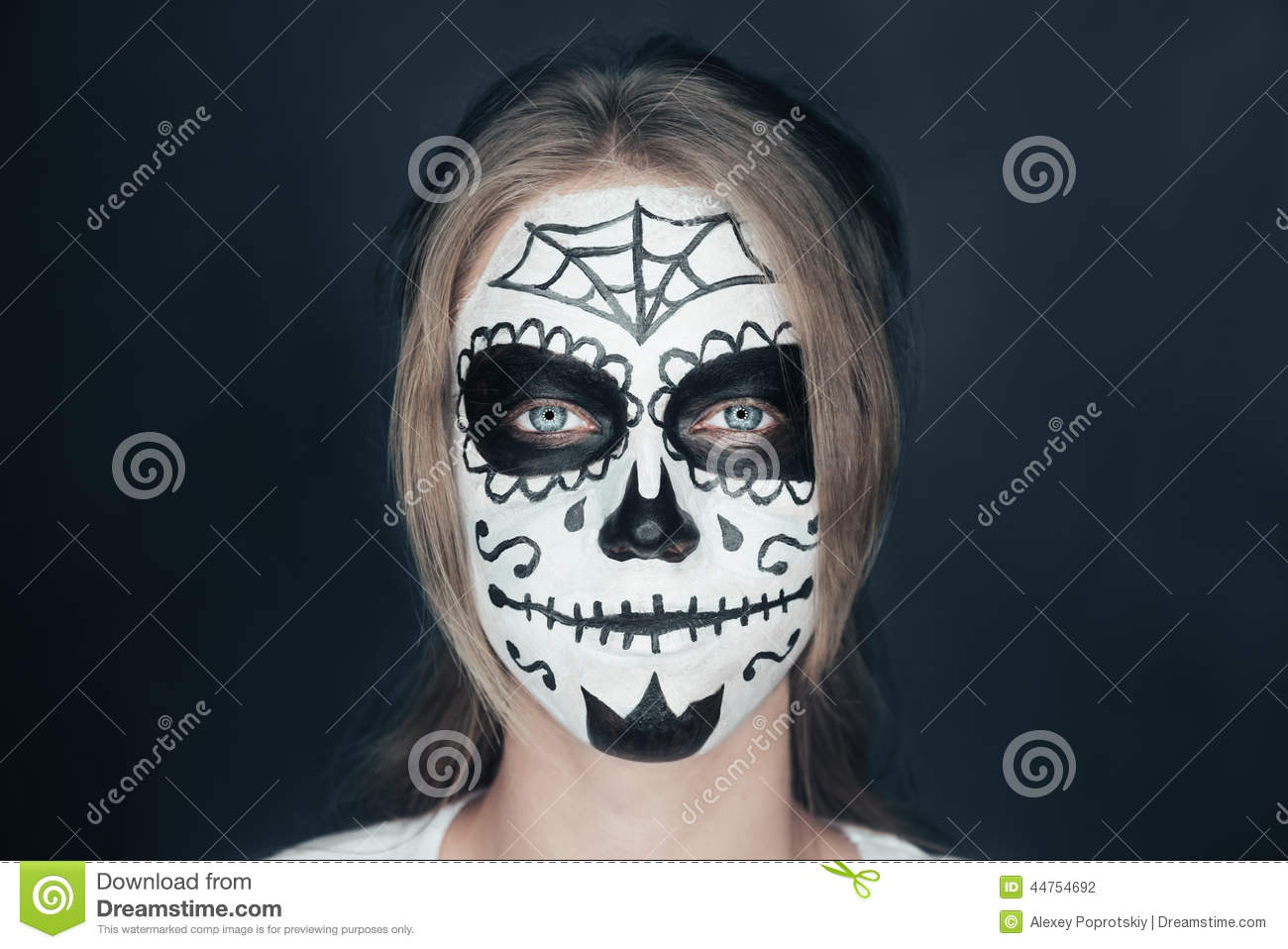portrait of smiling young woman with sugar skull makeup halloween face art