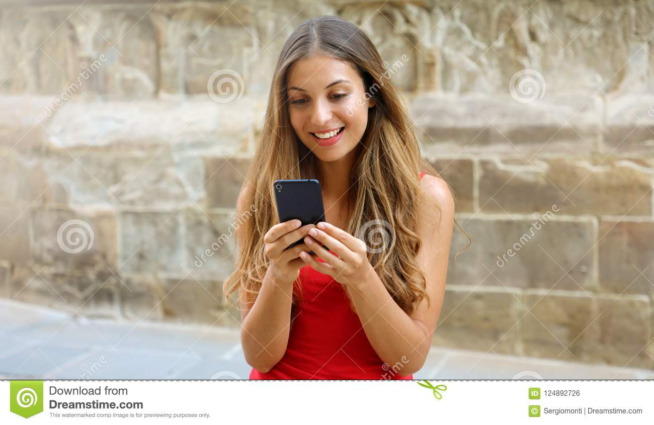 Smiling woman using mobile phone app to play video games online. City woman relaxing. Urban lifestyle. Banner crop for advertising