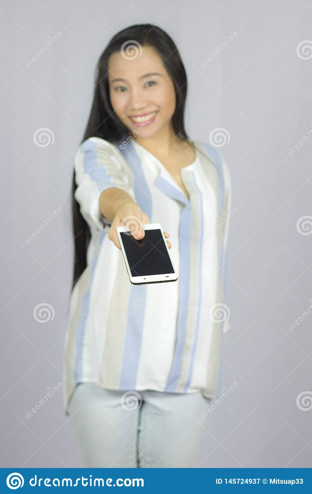 Smiling women holding mobile phone, give a smart phone to you. isolated on gray background