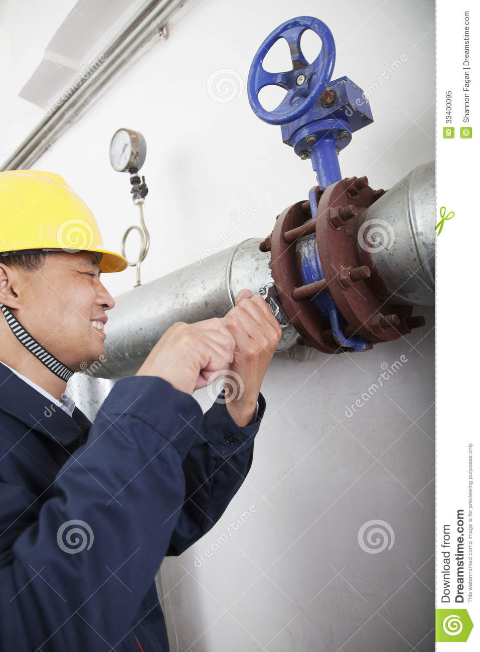 Smiling worker checking the oil pipeline equipment in a gas plant, Beijing, China