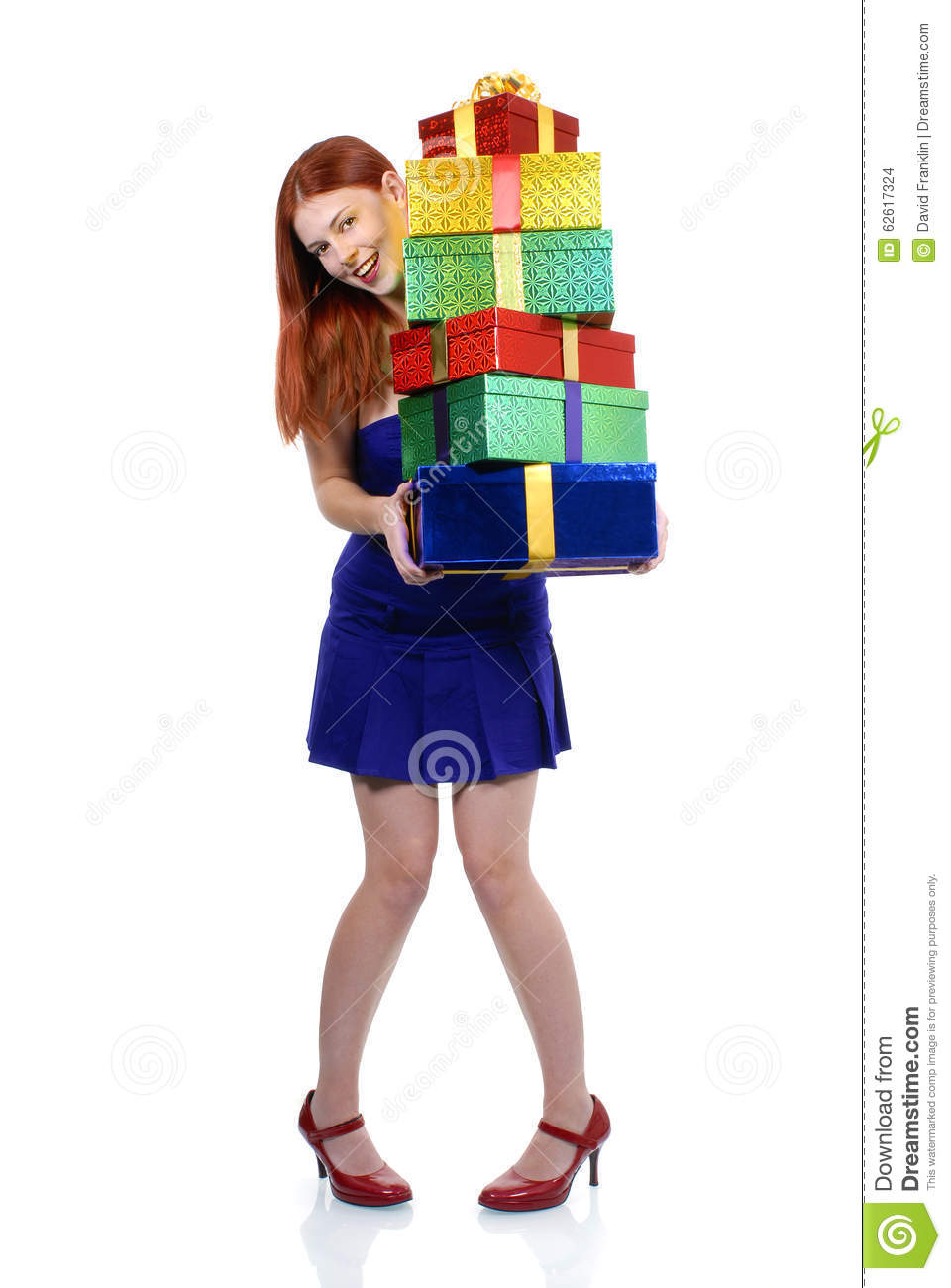 Smiling Young Adult Woman In Blue Christmas Or Birthday Party Dress Holding Pile Of Gifts