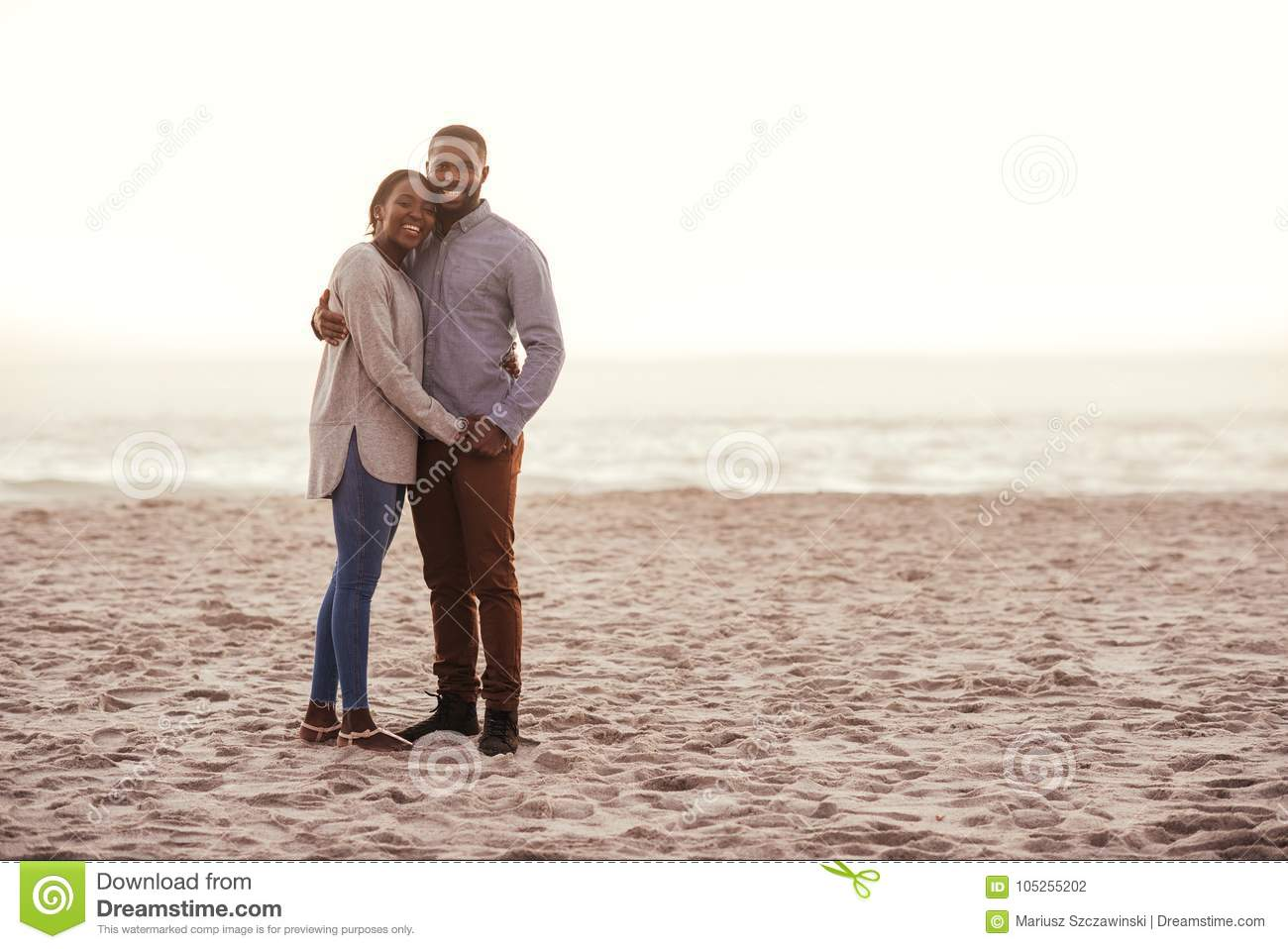 Smiling young African couple standing on a beach at sunset