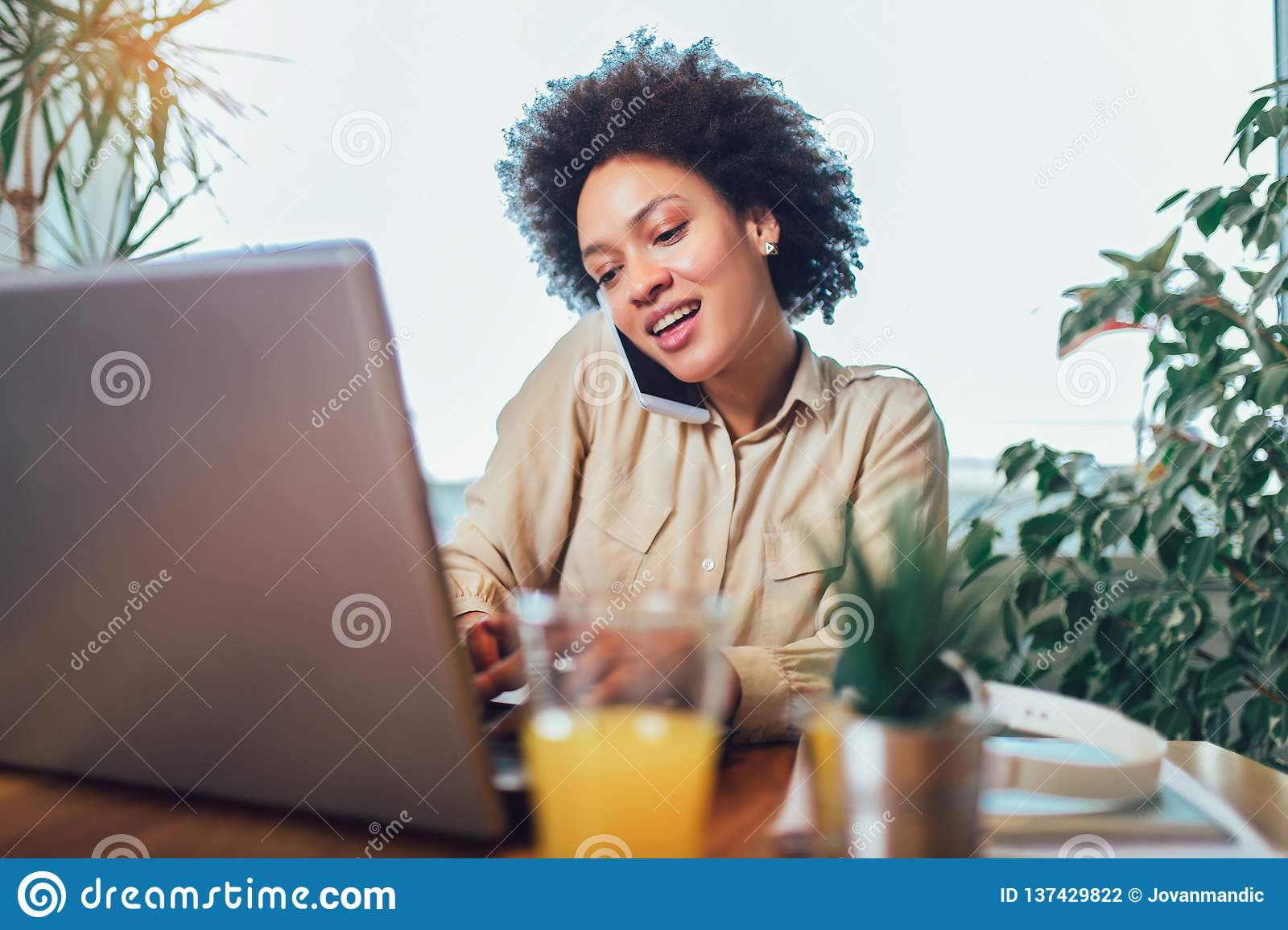 Smiling young African female entrepreneur sitting at a desk in her home office working online