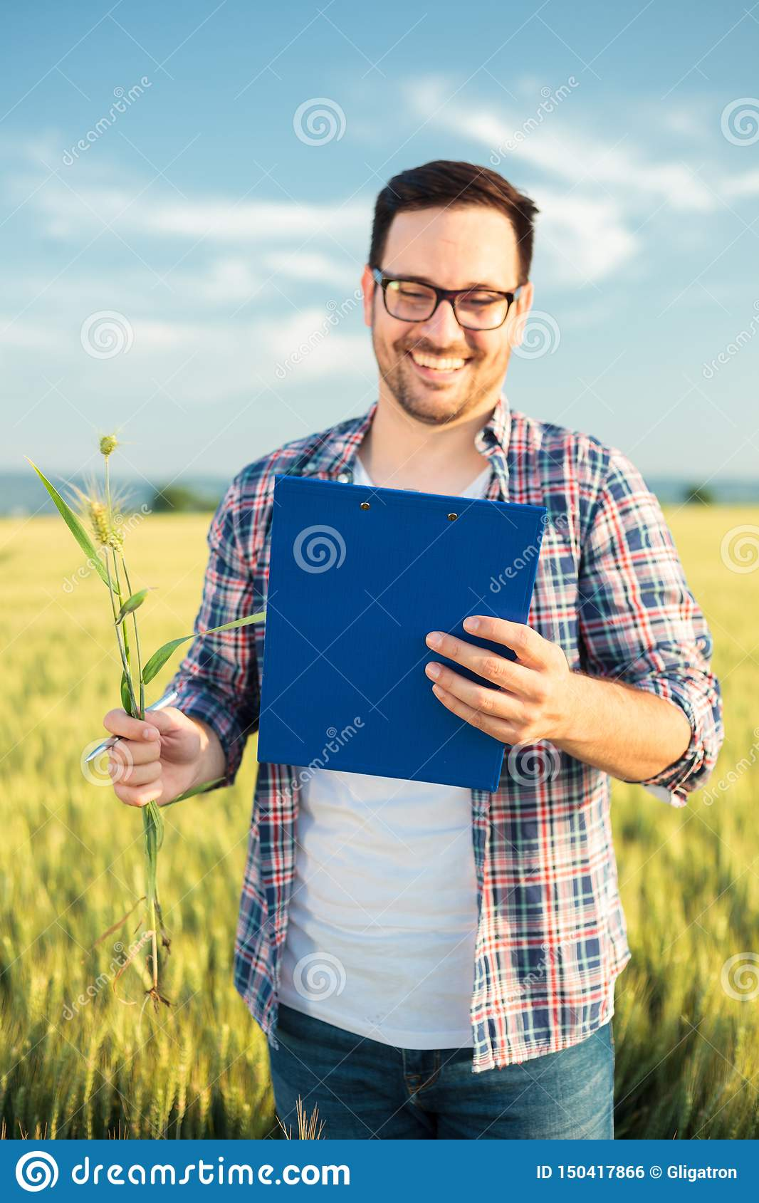 Smiling young agronomist or farmer inspecting wheat field before the harvest, writing data to a clipboard. Selective focus on fore