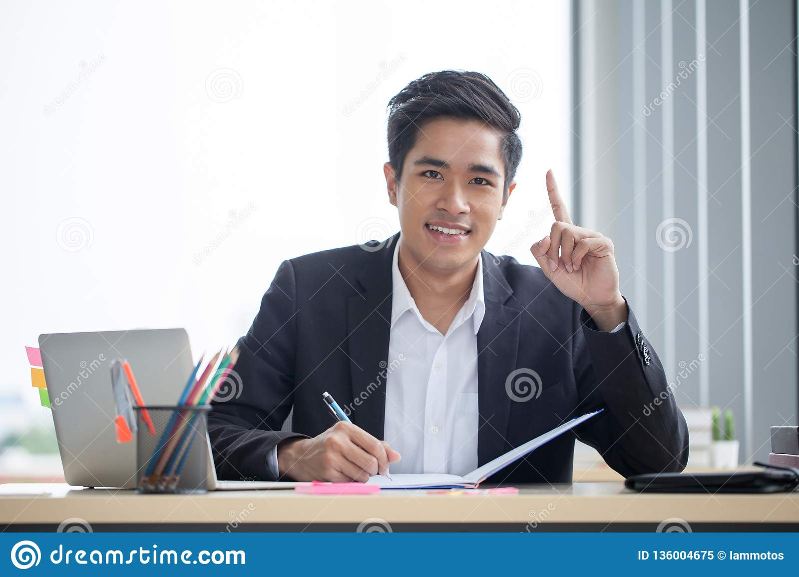 Smiling young asian business man working with note book on desk and Finger pointing up in a modern office