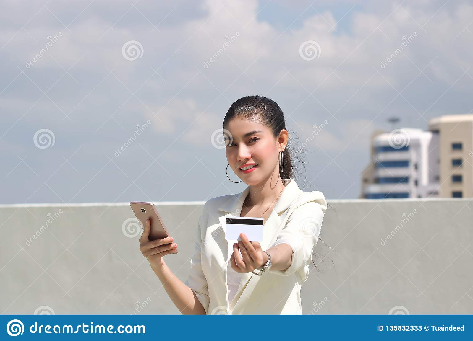 Smiling young Asian woman with mobile smart phone and credit card for shopping online