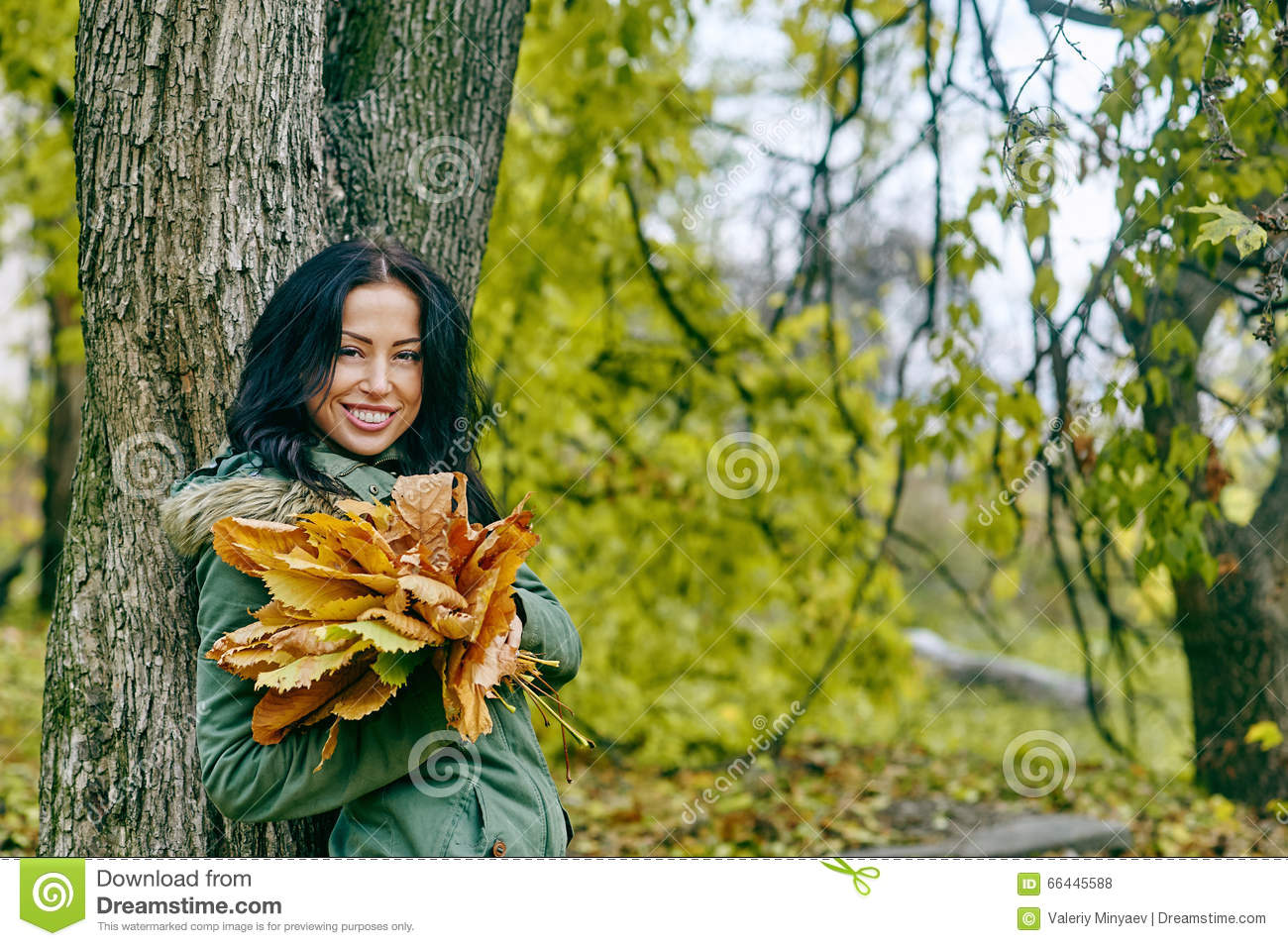 Smiling young attractive woman with autumn maple leaves in park at fall outdoors