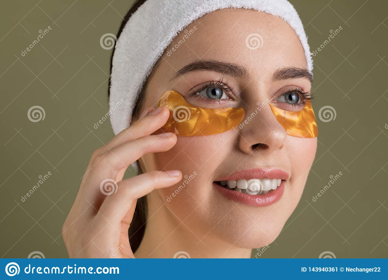 Smiling young beautiful woman in gold patches for eyes on green background