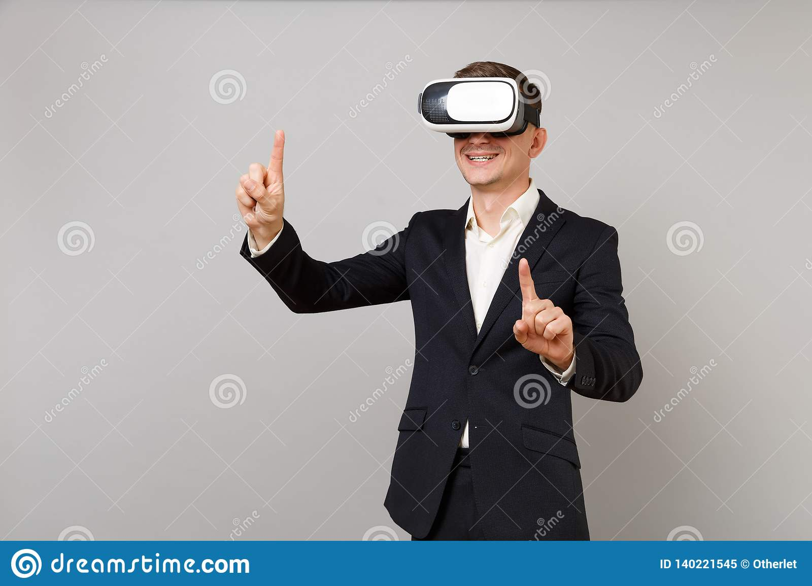 Smiling young business man looking in headset touch something like push click on button and pointing at floating virtual