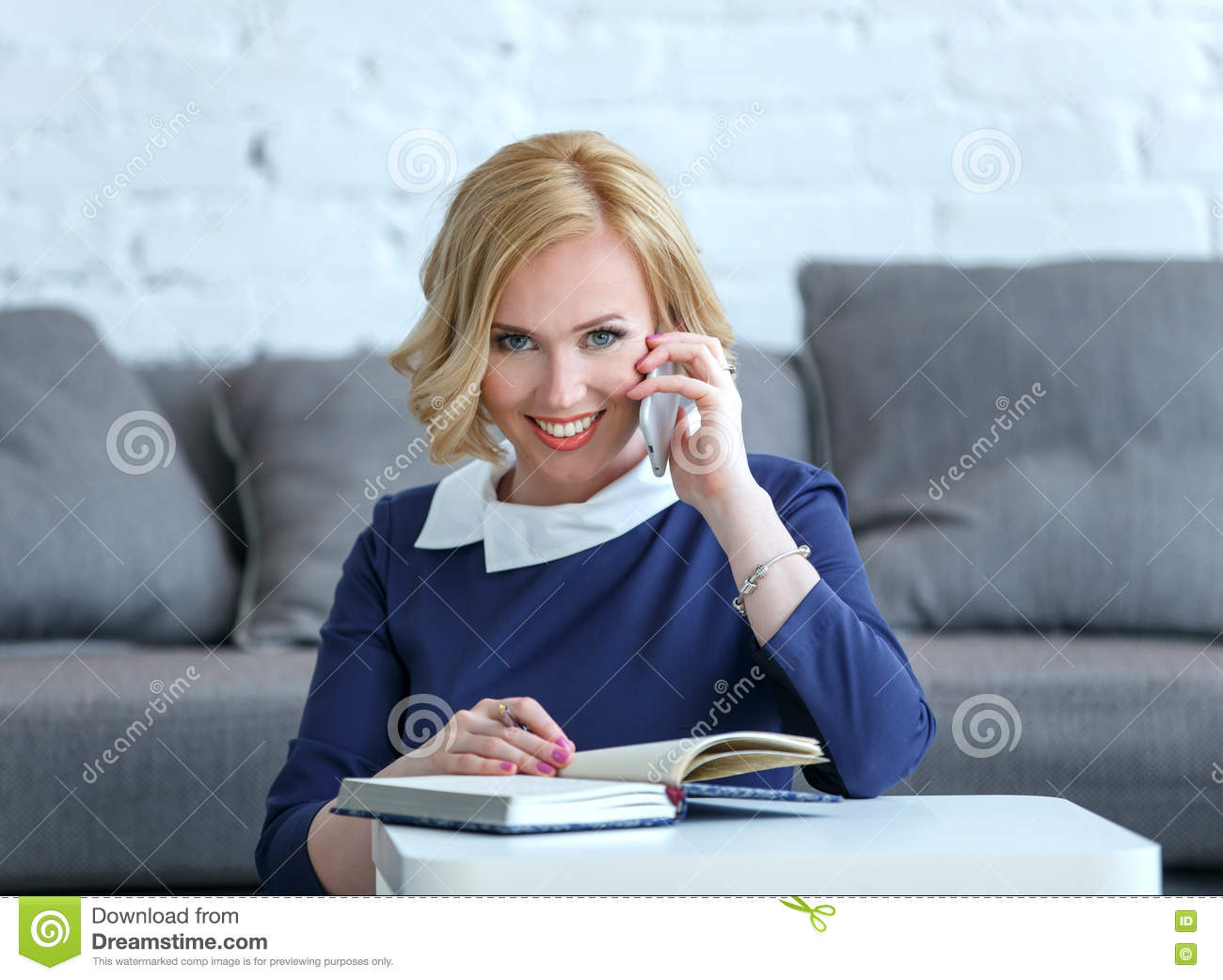 Smiling young business woman talking to the cell phone