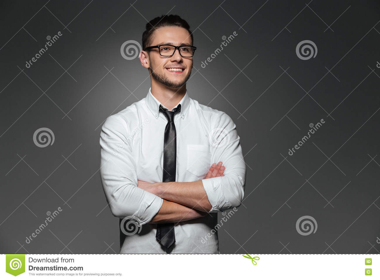 Smiling Young Businessman In Glasses Standing With Arms