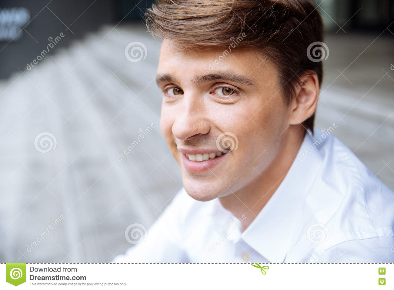 Smiling young businessman in white shirt sitting outdoors