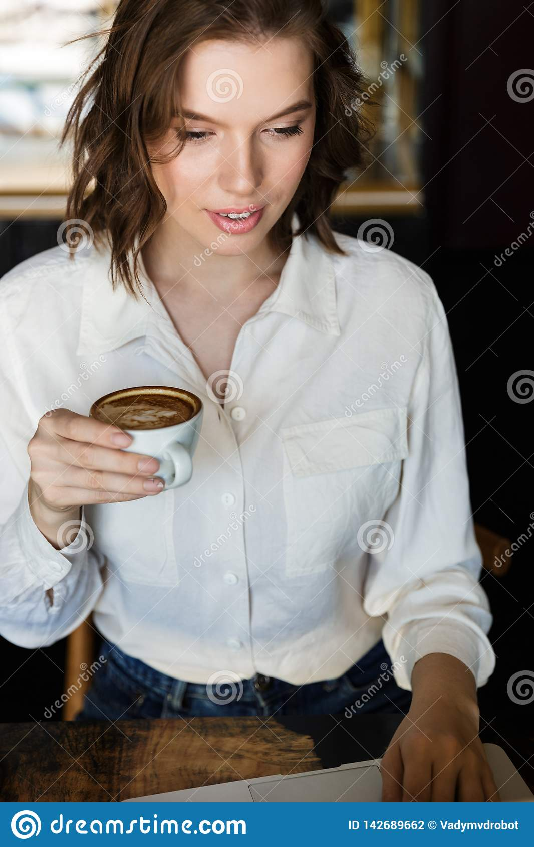 Smiling young businesswoman sitting at the cafe indoors