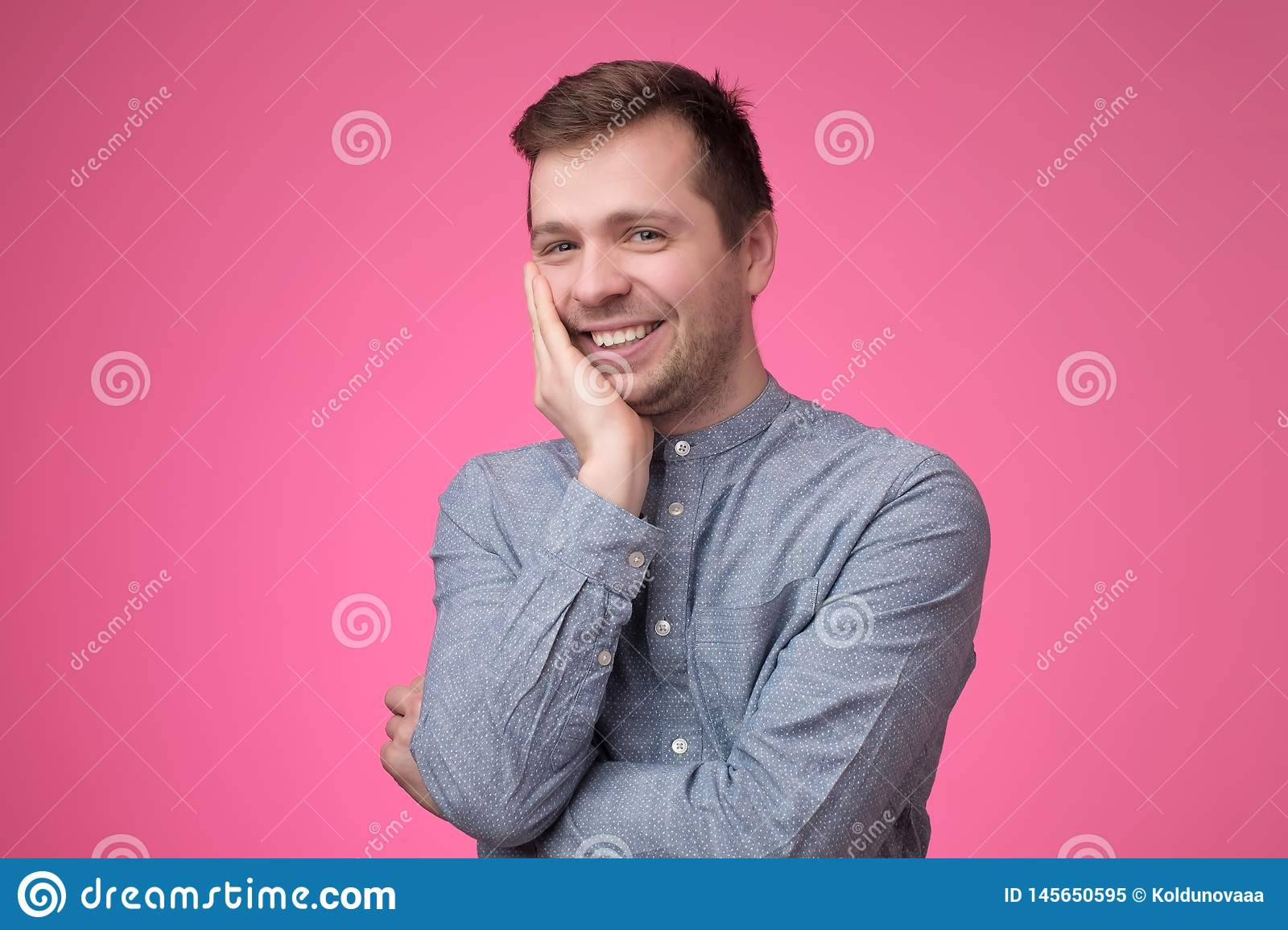 Smiling young caucasian man putting his hand to his chin