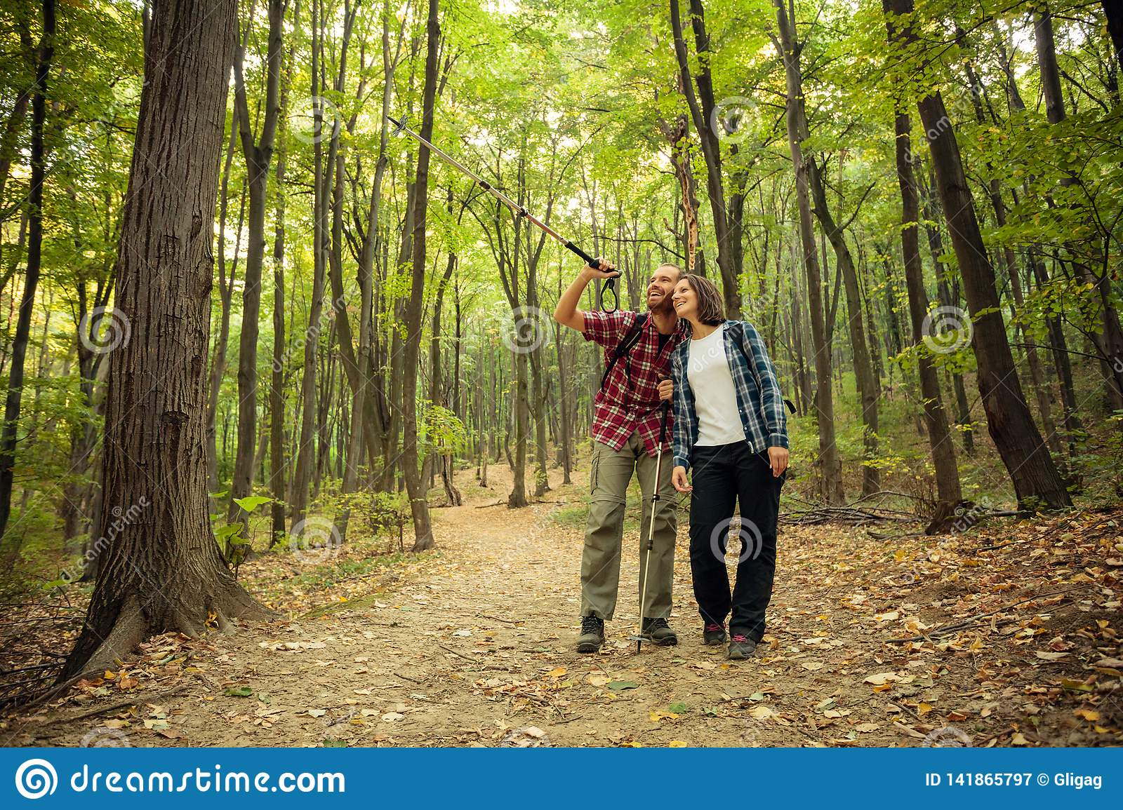Smiling young couple hiking through forest. Man is pointing to a distance