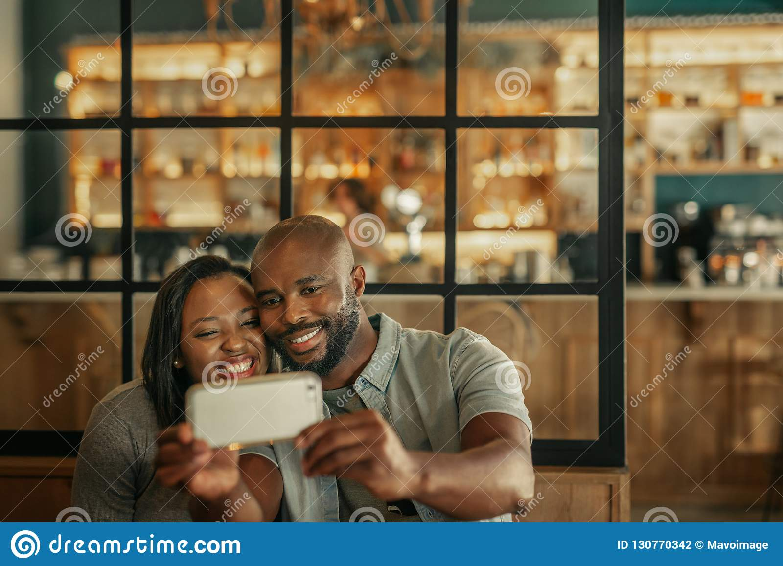 Smiling young couple taking selfies together in a bar