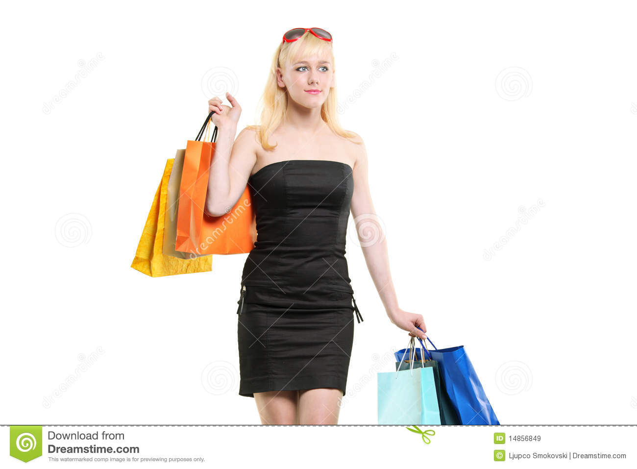A smiling young female posing with shopping bags