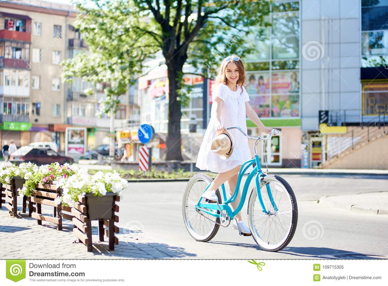 Smiling young female in white dress riding blue bike in front of modern city buildings on summer day