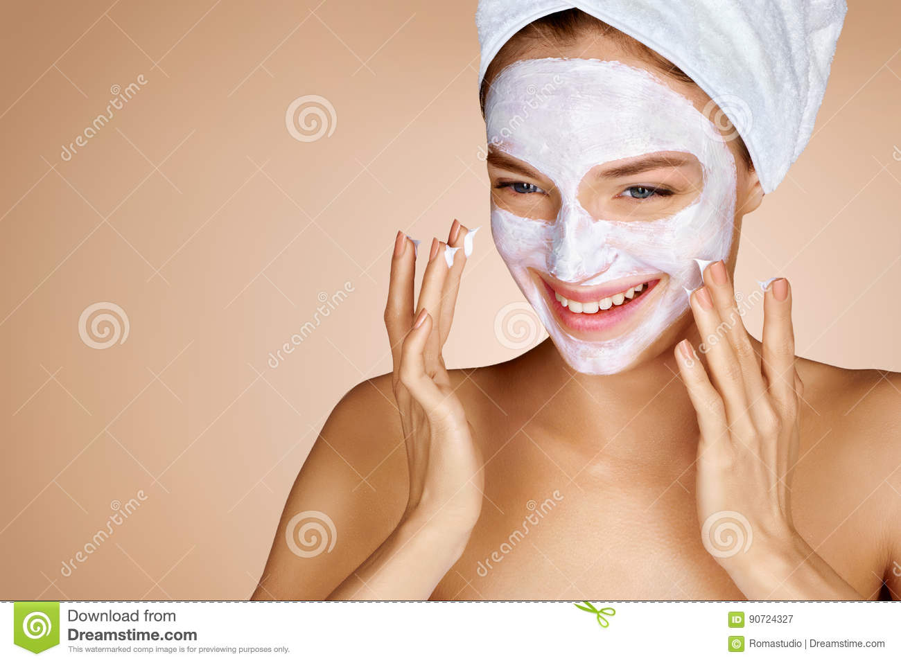Smiling young girl with cosmetic mask on her face