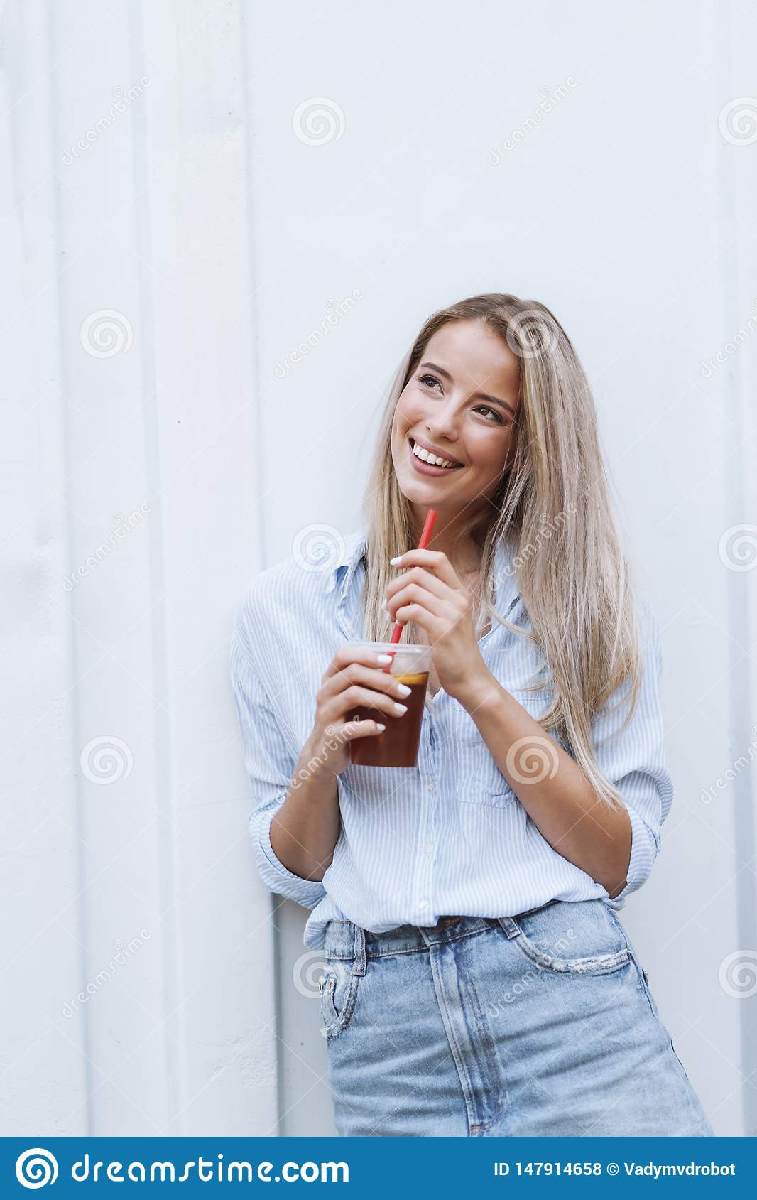 Smiling young girl drinking juice while standing