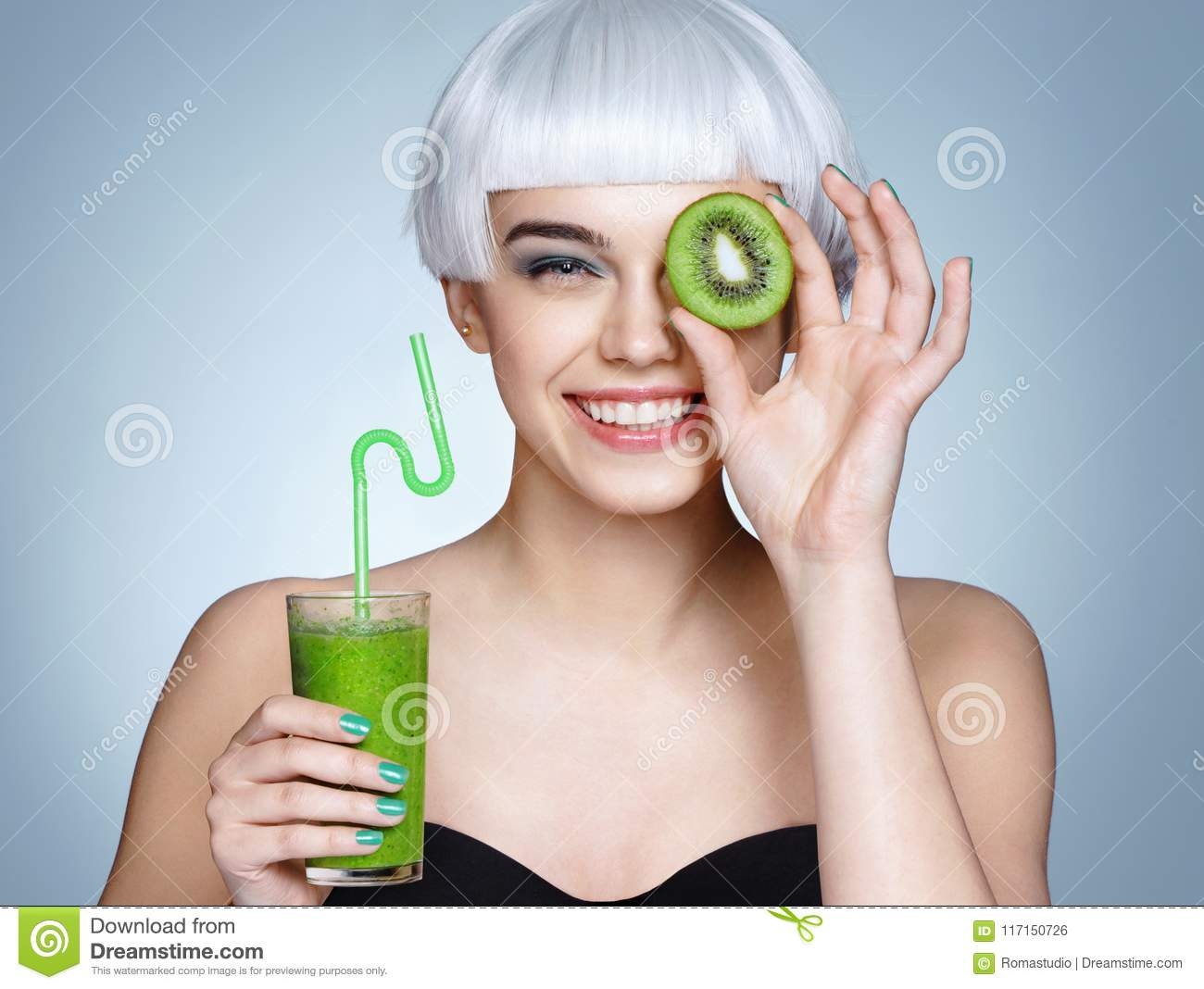 Smiling young girl holding smoothie detox cocktail of kiwi fruit