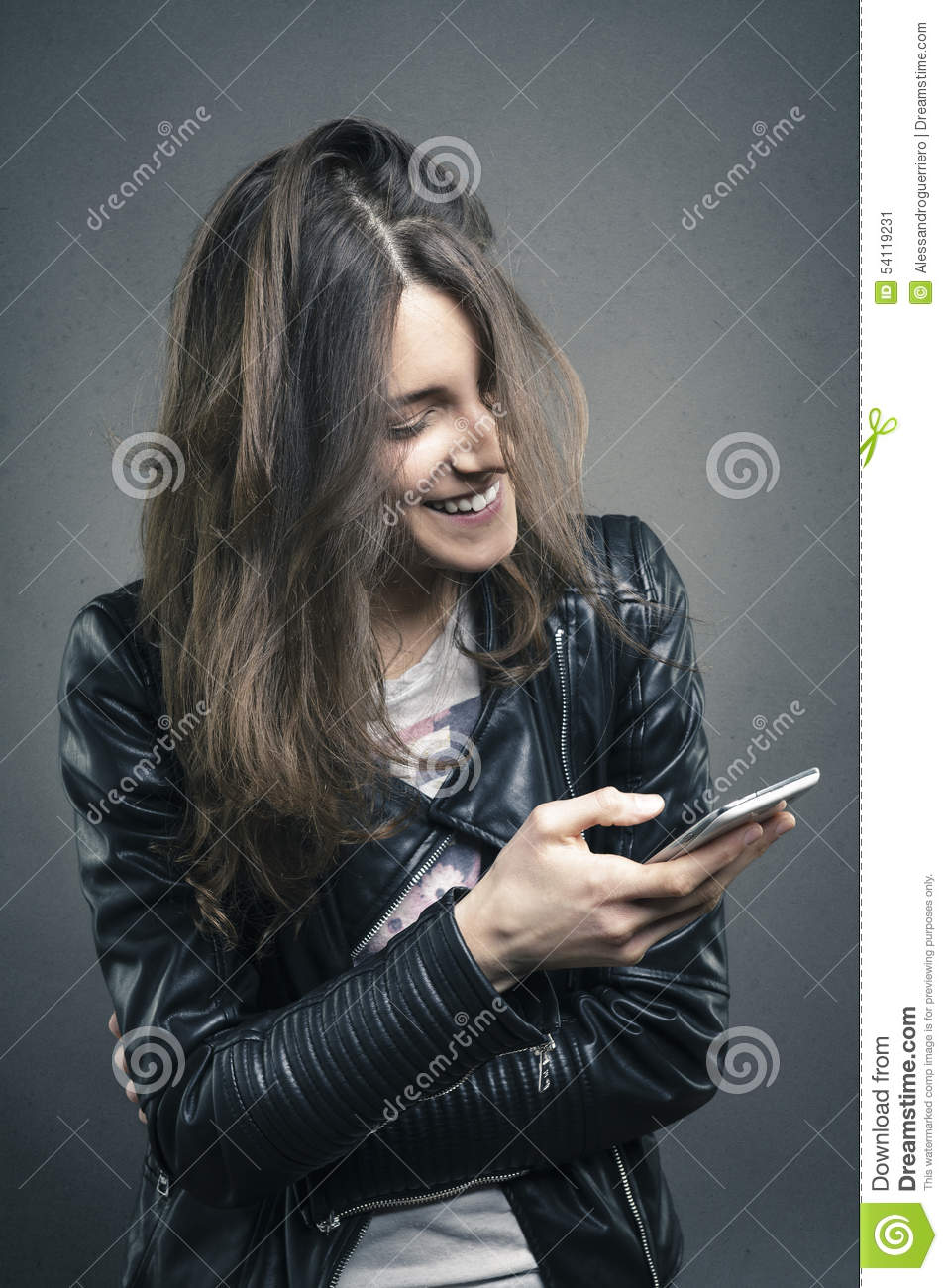 Smiling young girl looking at phone with amused emotion