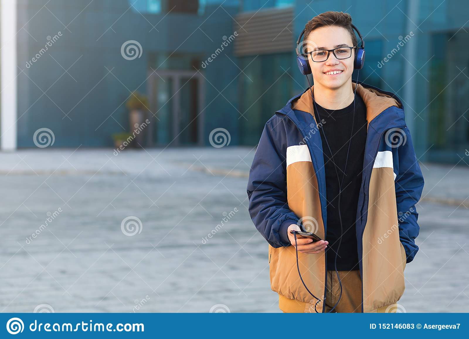 Smiling young guy listening to music, holding the phone outdoors. Copy space
