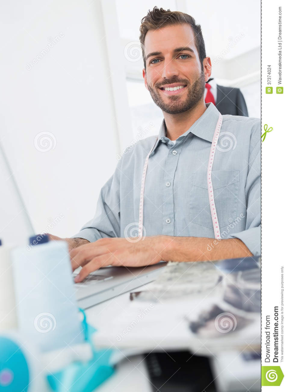 Smiling young male fashion designer using laptop stock for To be a fashion designer