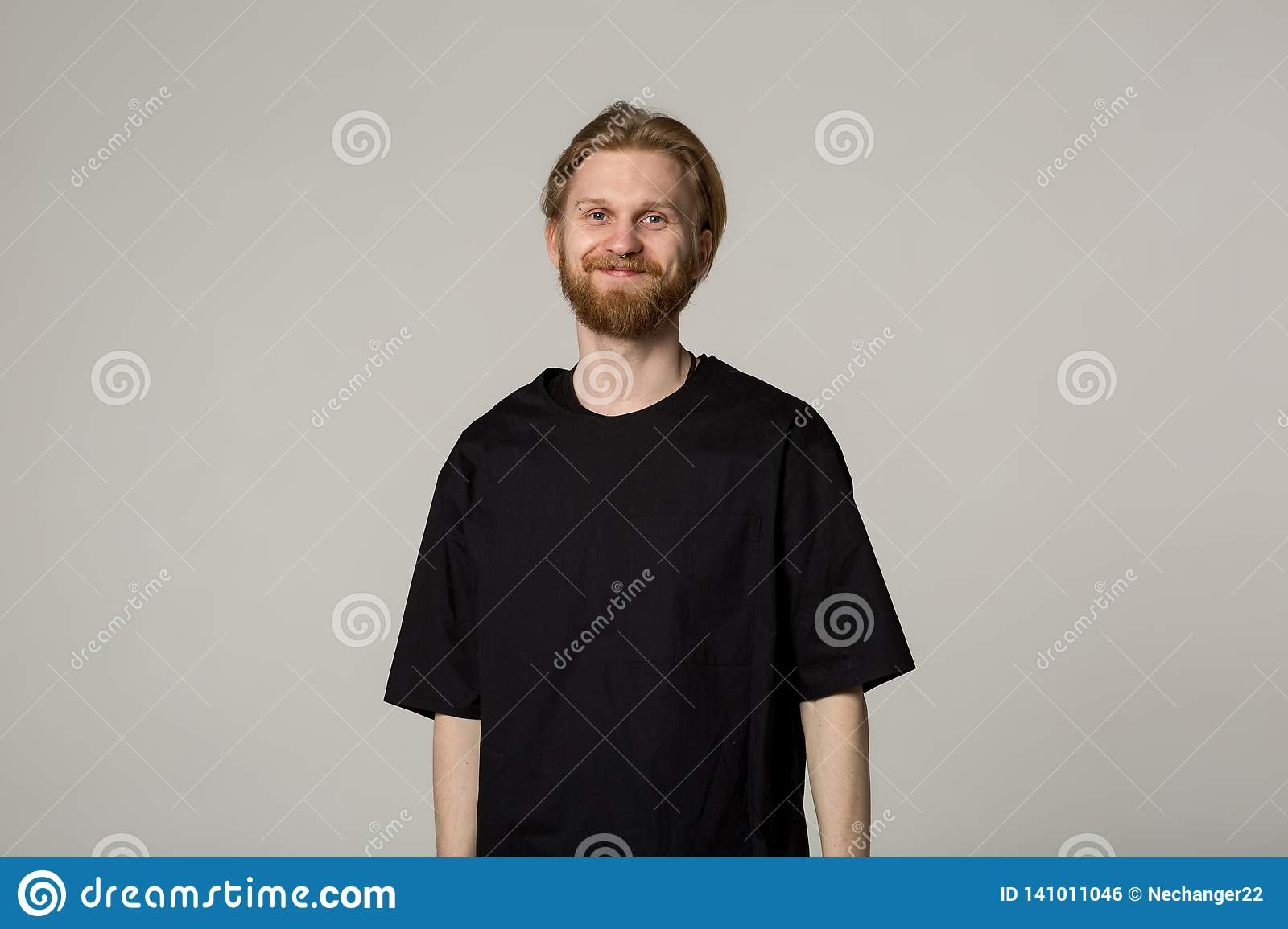 Smiling young man with beard in black shirt