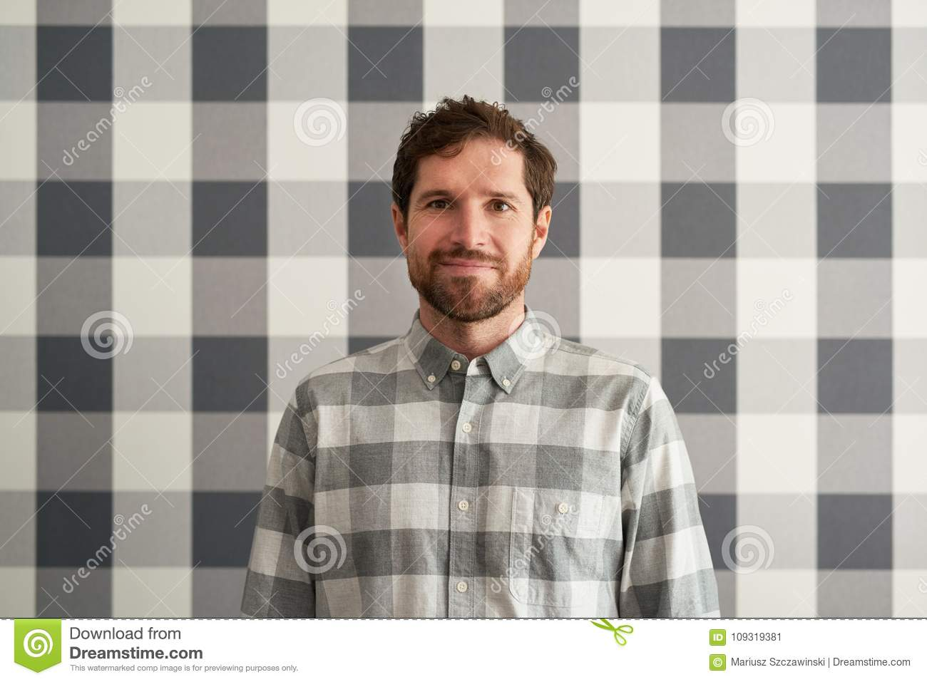 Smiling young man wearing a checkered shirt matching his wallpaper