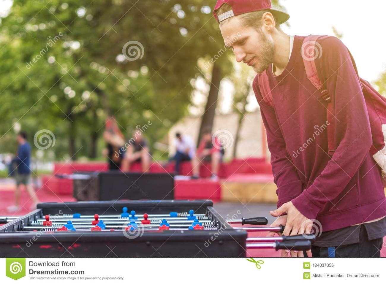 Smiling young man playing table soccer foosball outside having fun with friends d