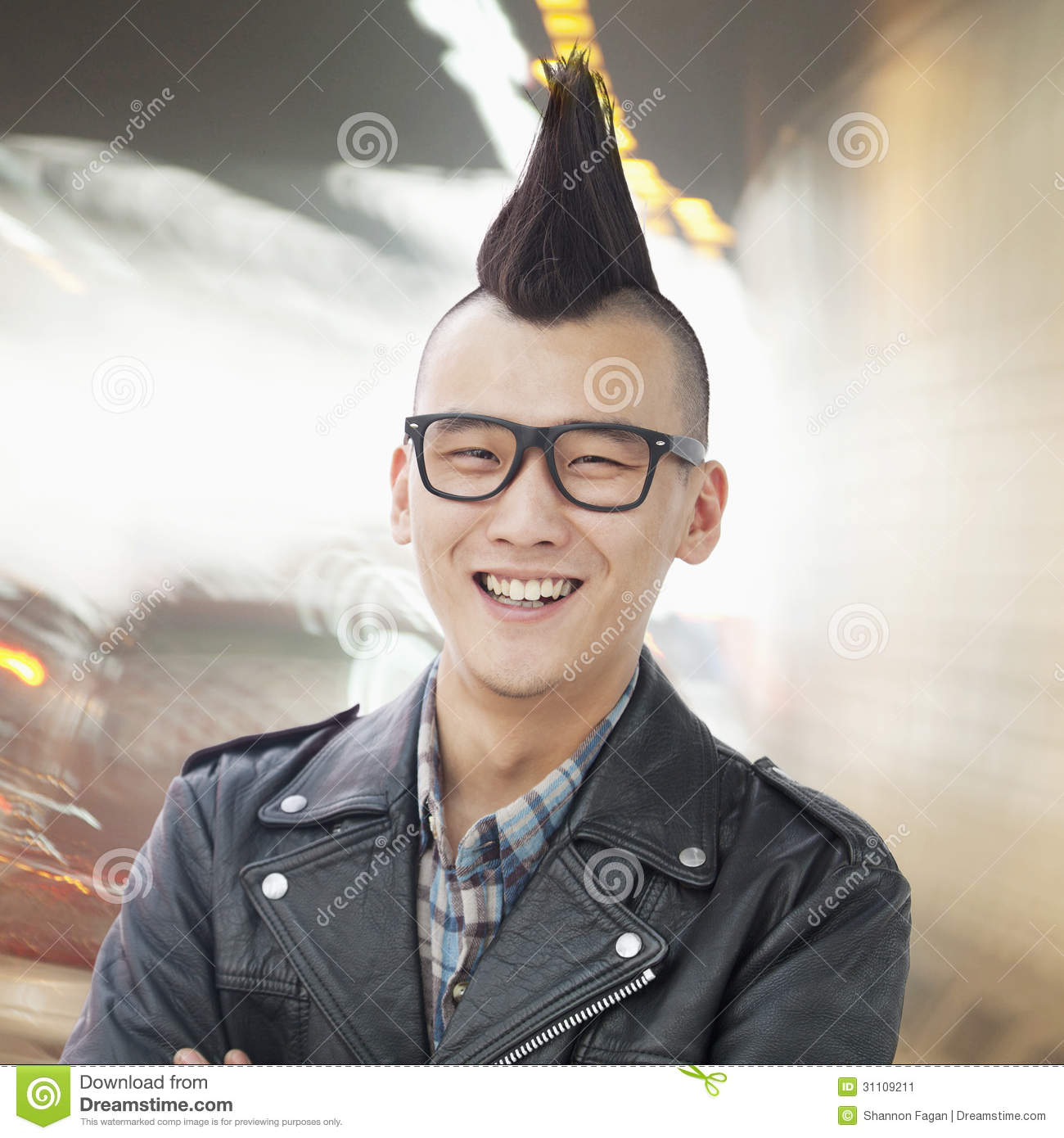 smiling young man with punk mohawk and glasses looking at