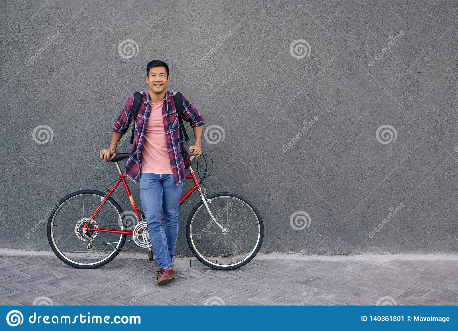 5b6526770 Portrait of a smiling young Asian man in a plaid shirt standing with his  bike in front of a gray wall in the city