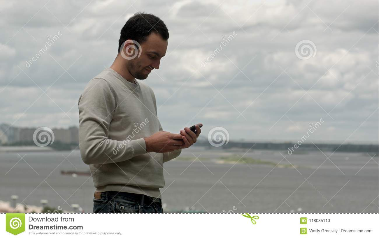 Smiling young man using a smartphone near the river.
