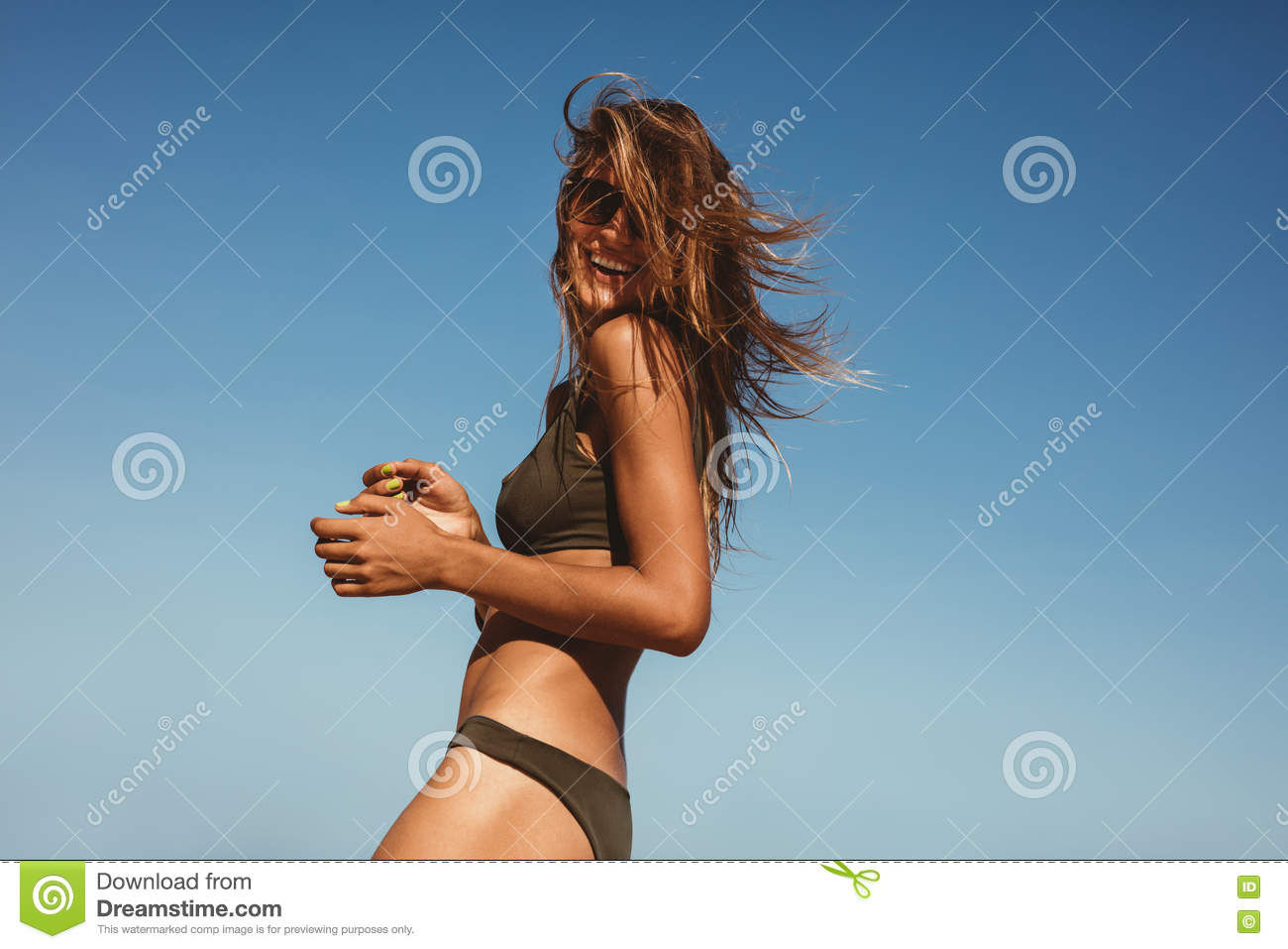 Smiling young model in bikini standing against blue sky