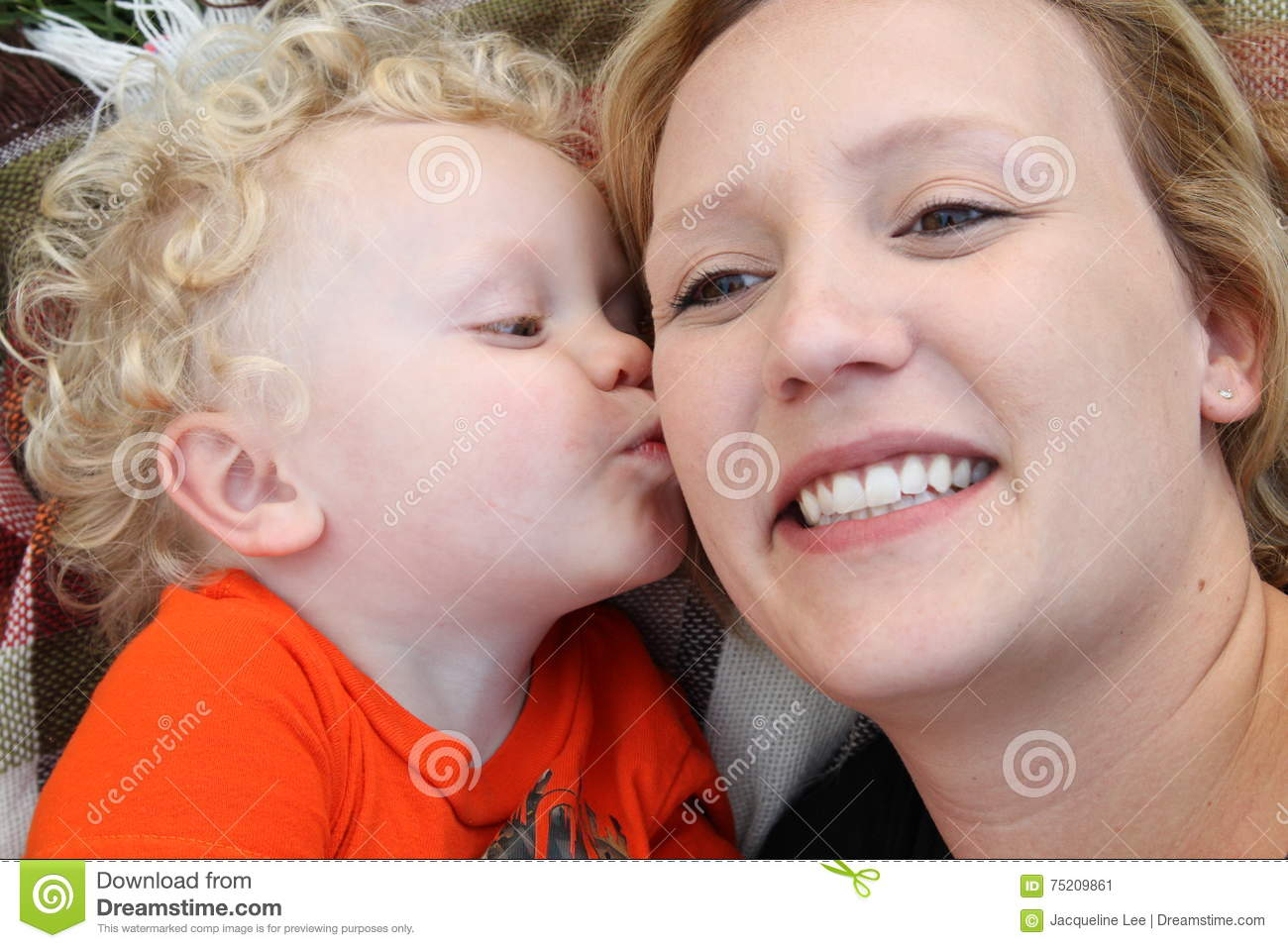 smiling young mother gets kiss from her little boy stock image