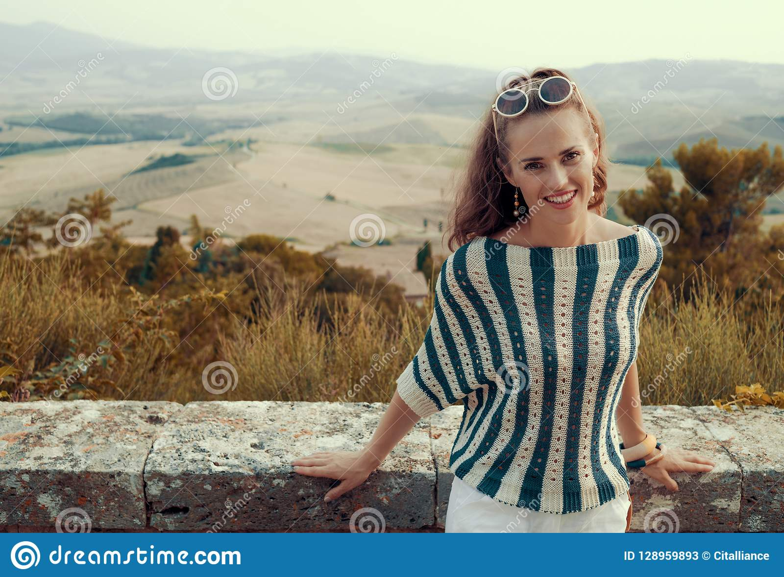 Smiling young tourist woman in front of scenery of Tuscany