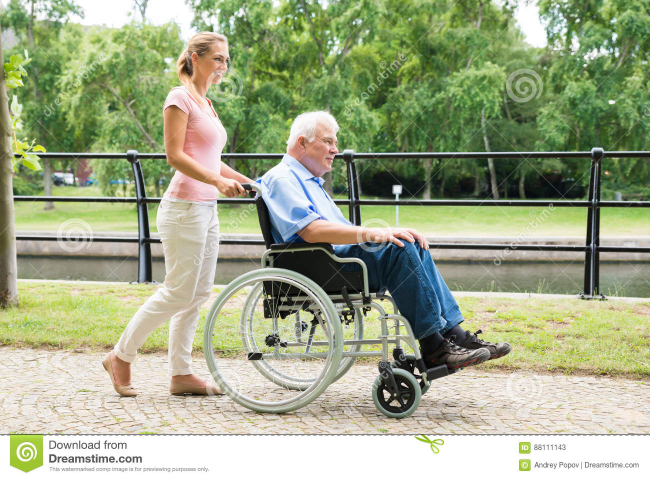 Smiling Young Woman Assisting Her Disabled Father On Wheelchair