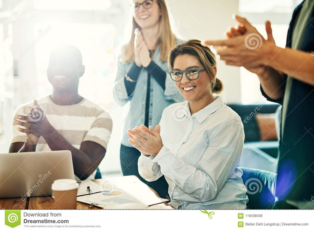 Smiling young woman clapping with colleagues in a modern office