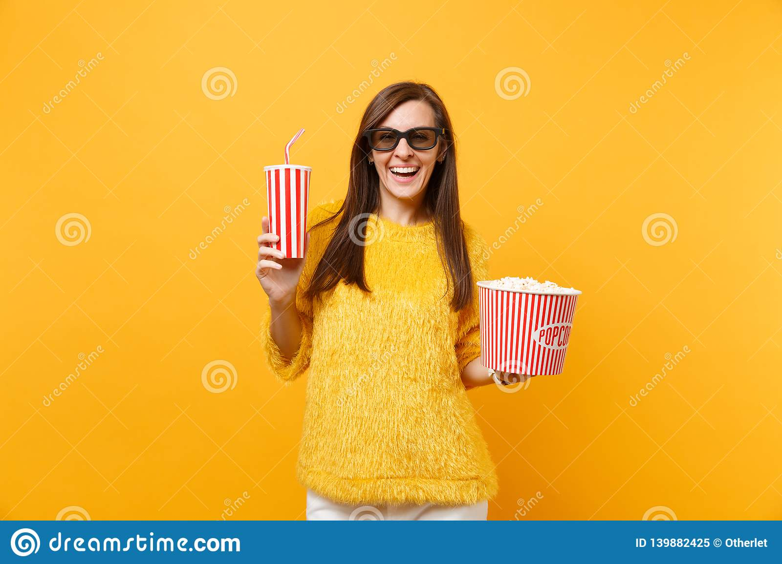 Smiling young woman in 3d imax glasses watching movie film, holding bucket of popcorn, plastic cup of cola or soda