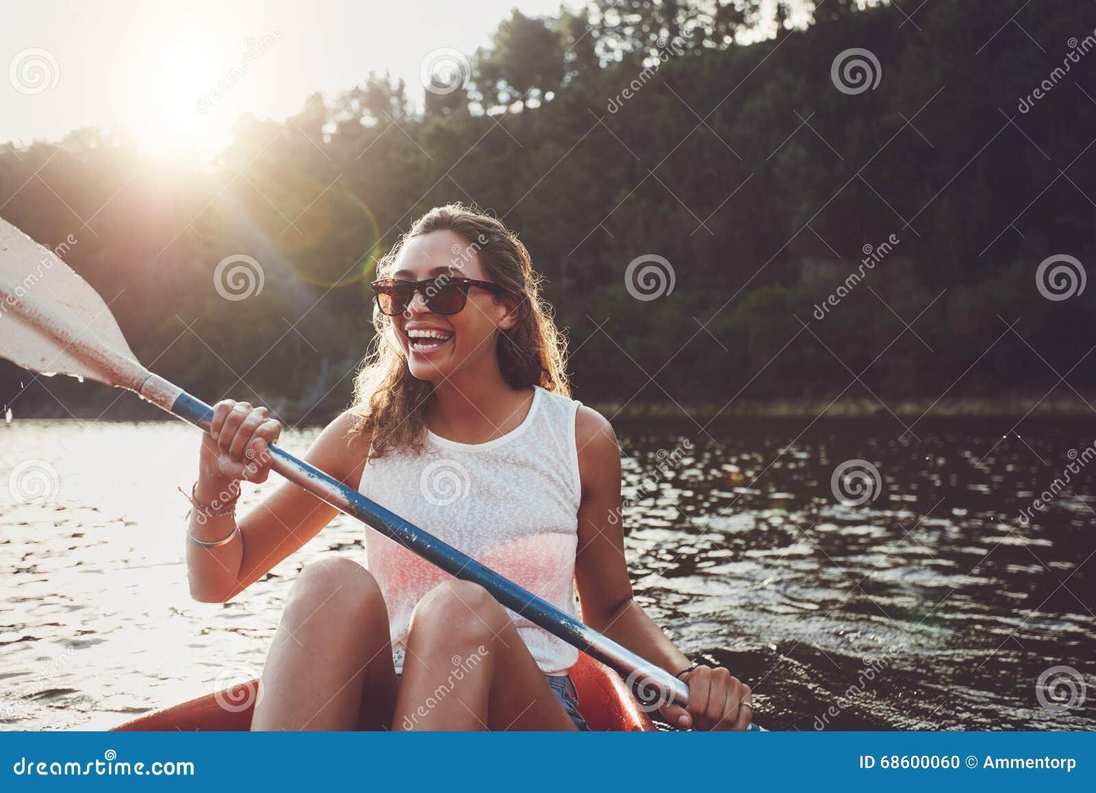 Smiling young woman kayaking on a lake
