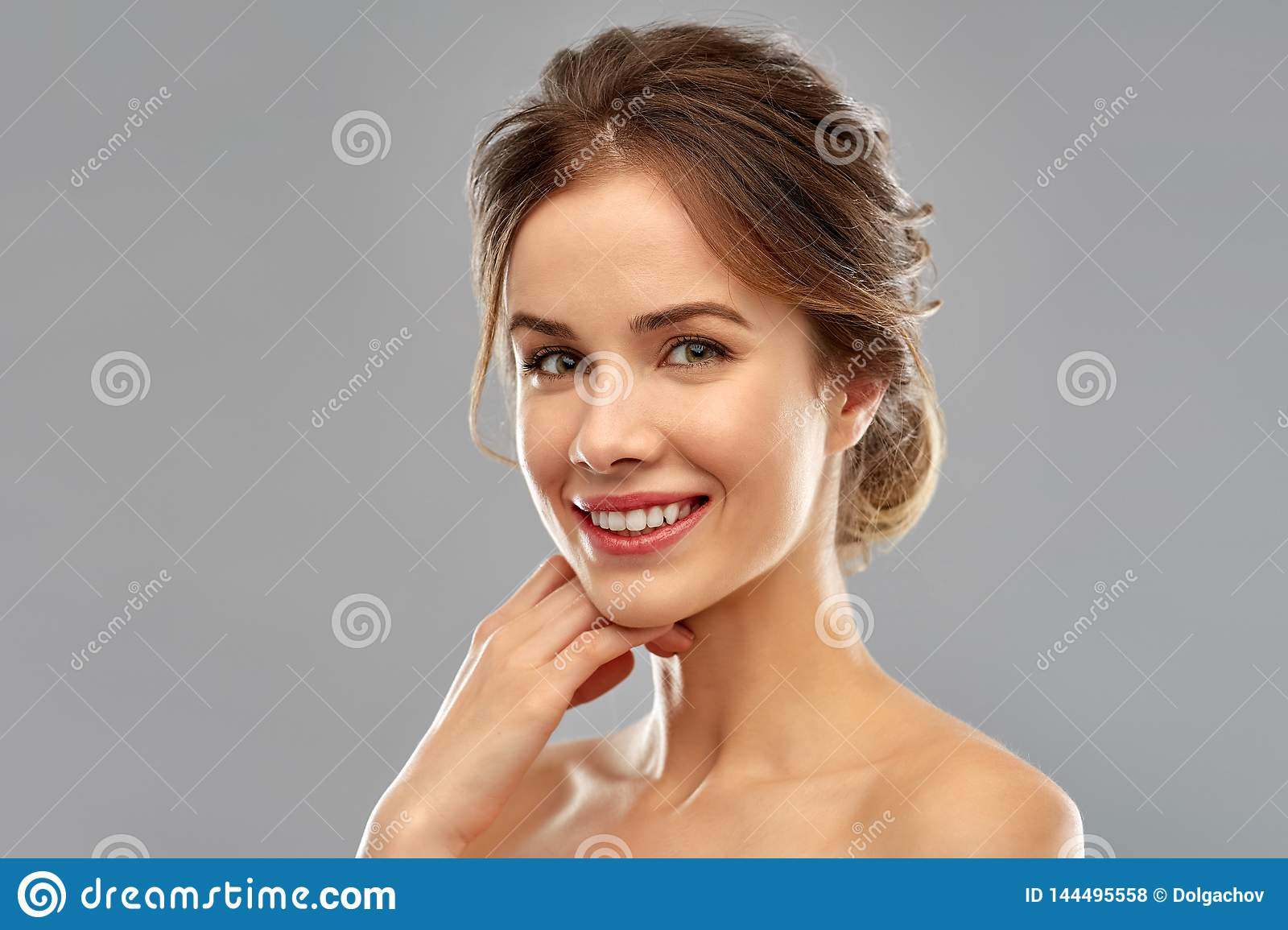 Smiling young woman over grey background